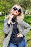Красивая молодая счастливая белокурая девушка в пальто, джинсах и солнечных очках идя в парк на солнечный день Стоковая Фотография