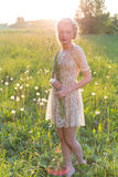 Красивая молодая сладостная девушка в белом платье с волосами на головных вкосую прогулках в поле на заходе солнца Стоковое Изображение RF