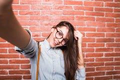 Красивая молодая темн-с волосами девушка в представлять вскользь одежд и eyeglasses, Стоковые Изображения