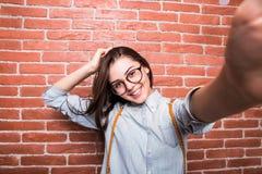 Красивая молодая темн-с волосами девушка в представлять вскользь одежд и eyeglasses, Стоковое Фото