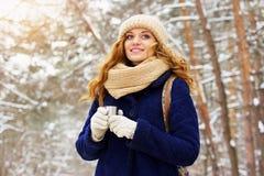Красивая молодая усмехаясь девушка в синем пиджаке и с сумкой на ее назад и выпивая чае Девушка перемещения Стоковое Фото