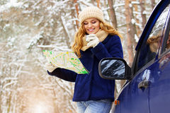 Красивая молодая усмехаясь девушка в синем пиджаке стоя около автомобиля, держа карту в руке и выпивая чай Девушка перемещения Стоковая Фотография