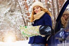 Красивая молодая усмехаясь девушка в синем пиджаке стоя около автомобиля, держа карту в руке и выпивая чай Девушка перемещения Стоковое Изображение RF
