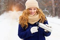 Красивая молодая усмехаясь девушка в чае синего пиджака лить от thermocup Девушка перемещения Стоковая Фотография RF