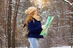 Красивая молодая усмехаясь девушка держа карту в ее руках, нося синем пиджаке и с сумкой на ей назад Девушка перемещения Стоковое Изображение