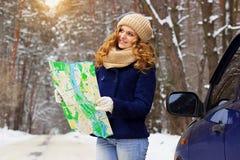 Красивая молодая усмехаясь девушка держа карту и положение на дороге около автомобиля, нося синий пиджак Девушка перемещения Стоковое Изображение
