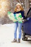 Красивая молодая усмехаясь девушка держа карту стоя около автомобиля на дороге, нося синем пиджаке Девушка перемещения Стоковые Фото