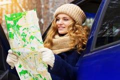 Красивая молодая усмехаясь девушка сидит в автомобиле и карта держать в ее руках, нося синий пиджак Девушка перемещения Стоковое Изображение