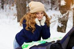 Красивая молодая усмехаясь девушка смотря в карте на bonnet автомобиля, нося синий пиджак Девушка перемещения Стоковое фото RF