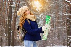Красивая молодая усмехаясь девушка стоя на дороге и держа карту в ее руках с сумкой на ей назад Стоковая Фотография RF