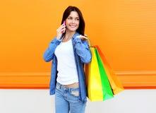 Красивая молодая усмехаясь женщина с хозяйственными сумками Стоковое Фото