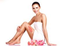 Красивая молодая усмехаясь женщина с цветками используя scrub. Стоковое Изображение RF