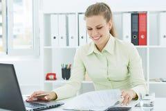 Красивая молодая усмехаясь секретарша работая при бумаги сидя на офисе стоковая фотография rf