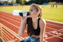 Красивая молодая утомленная питьевая вода девушки фитнеса после разминки Стоковые Фото