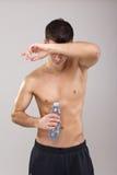 Красивая молодая утомленная питьевая вода парня во время разминки Стоковое фото RF