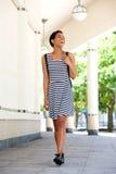 Красивая молодая чернокожая женщина идя снаружи в striped платье Стоковая Фотография RF