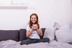 Красивая, молодая, redheaded женщина наслаждается ее кофе Стоковое Изображение