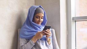 Красивая мусульманская девушка используя Smartphone в кафе Современная мусульманская женщина и новые технологии Стоковая Фотография RF