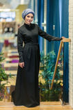 Красивая мусульманская женщина в современном восточном платье стоя в фойе ресторана Стоковые Изображения RF