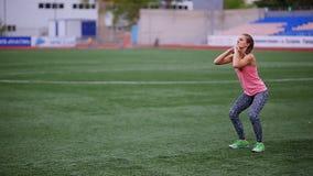 Красивая мышечная девушка в колготках и жилете делает подогрев на стадионе Crossfit, фитнес, здоровый образ жизни акции видеоматериалы
