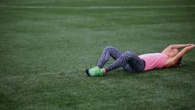 Красивая мышечная девушка в колготках и жилете делает подогрев на стадионе Перекрестная пригонка, фитнес, здоровый образ жизни видеоматериал