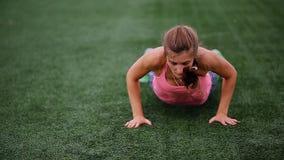 Красивая мышечная девушка в колготки и жилете делает burpee на стадионе Crossfit, фитнес, здоровый образ жизни видеоматериал