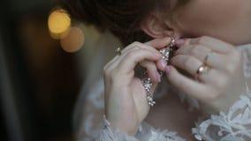 Красивая невеста внутри кладет дальше серьгу Девушка красоты модельная носит ювелирные изделия для замужества Wedding женский пор стоковое фото rf
