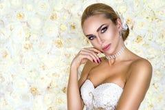 Красивая невеста в белом платье свадьбы на предпосылке стены цветков r стоковые фото
