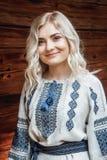 Красивая невеста в вышитой рубашке на предпосылке деревянного дома стоковые изображения rf