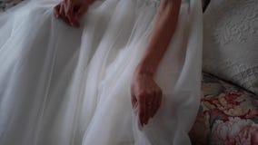 Красивая невеста в длинном белом платье сидит на софе в комнате акции видеоматериалы