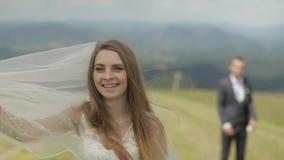 Красивая невеста в платье свадьбы и вуаль на горах ( акции видеоматериалы