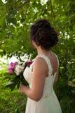 Красивая невеста в платье свадьбы с букетом пионов Стоковая Фотография RF