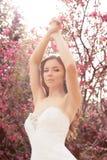 Красивая невеста в платье свадьбы, представляя весной сад цветения Стоковые Фото