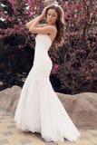 Красивая невеста в платье свадьбы, представляя весной сад цветения Стоковое Изображение RF