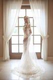 Красивая невеста в платье свадьбы при длинная bridal вуаль представляя мимо Стоковая Фотография RF