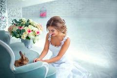 Красивая невеста в платье свадьбы с кроликом на его руках Стоковое Изображение RF