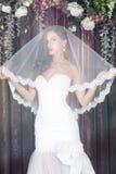 Красивая невеста в платье свадьбы с чуть-чуть плечами и вуалью стоковые фотографии rf