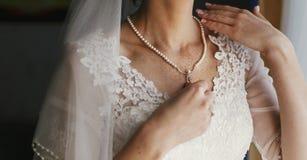 Красивая невеста держа дорогое серебряное ожерелье с жемчугами дальше Стоковые Фотографии RF