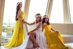Красивая невеста и 2 bridesmaids в желтых подобных платьях совместно в ресторане моря Стоковые Фотографии RF