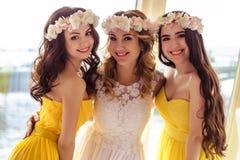 Красивая невеста и 2 bridesmaids в желтых подобных платьях совместно в ресторане моря Стоковая Фотография