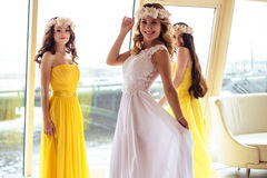 Красивая невеста и 2 bridesmaids в желтых подобных платьях совместно в ресторане моря Стоковое Изображение RF