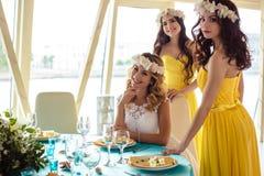 Красивая невеста и 2 bridesmaids в желтых подобных платьях совместно в ресторане моря Стоковая Фотография RF