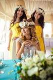 Красивая невеста и 2 bridesmaids в желтых подобных платьях совместно в ресторане моря Стоковые Изображения