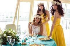 Красивая невеста и 2 bridesmaids в желтых подобных платьях совместно в ресторане моря Стоковое Изображение