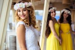 Красивая невеста и 2 bridesmaids в желтых подобных платьях совместно в ресторане моря Стоковые Фото