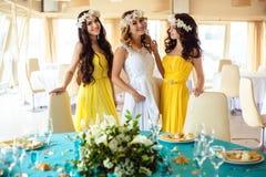 Красивая невеста и 2 bridesmaids в желтых подобных платьях совместно в ресторане моря Стоковое фото RF
