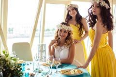 Красивая невеста и 2 bridesmaids в желтых подобных платьях совместно в ресторане моря Стоковые Изображения RF