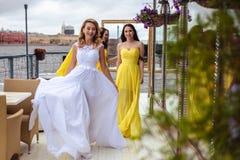 Красивая невеста и 2 bridesmaids совместно на террасе лета ресторан моря Стоковые Изображения