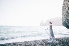 Красивая невеста молодой женщины в длинном платье около моря стоковые изображения rf