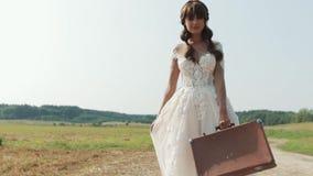 Красивая невеста наслаждаясь в платье свадьбы в солнечном парке акции видеоматериалы